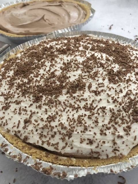 easy chocolate pudding cream pies with graham cracker crusts , one has fresh whipped cream on top with milk chocolate shavings