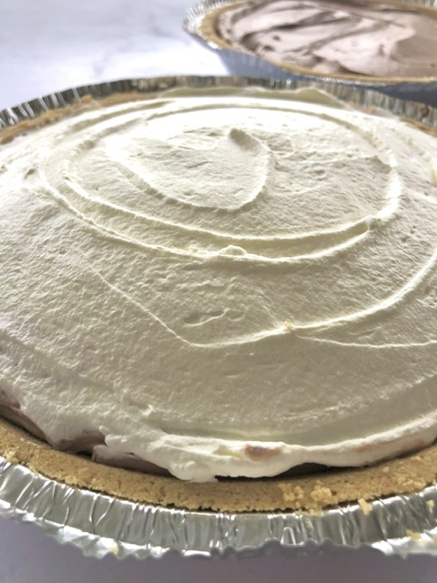 fresh whipped cream on top of the chocolate cream pie with a graham cracker crust