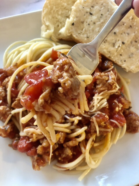 bite of slow cooker spaghetti with diced tomatoes and sausage