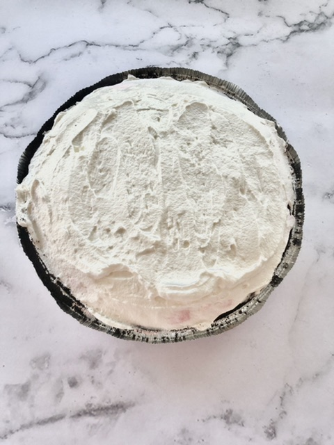 Fresh whipped cream spread on top of the no bake peppermint pie