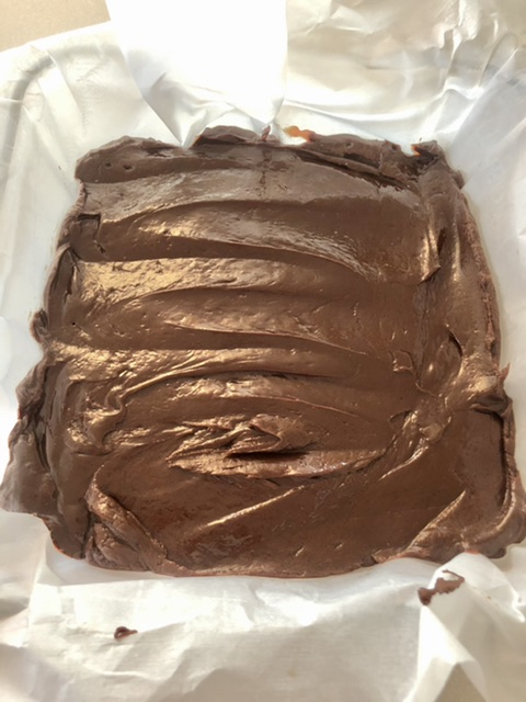 easy chocolate fudge pored and smoothed out in a 8x8 baking dish lined with parchment paper for candy cane fudge