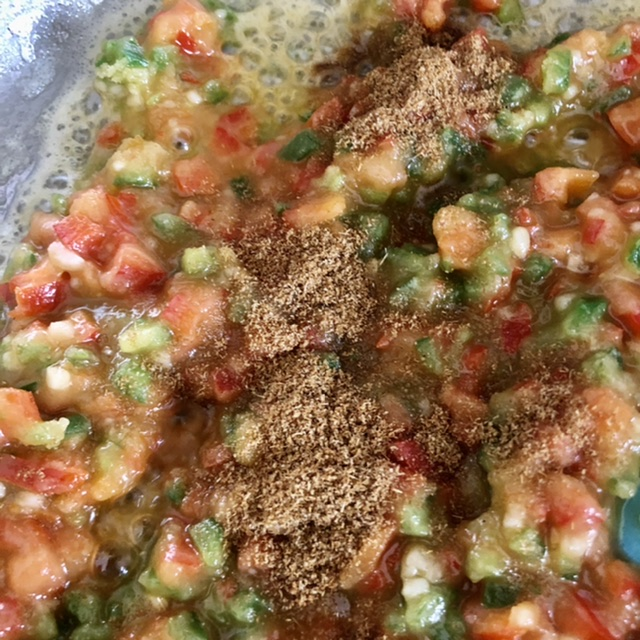 cumin added to red pepper and jalapeno in roux ready to mix together