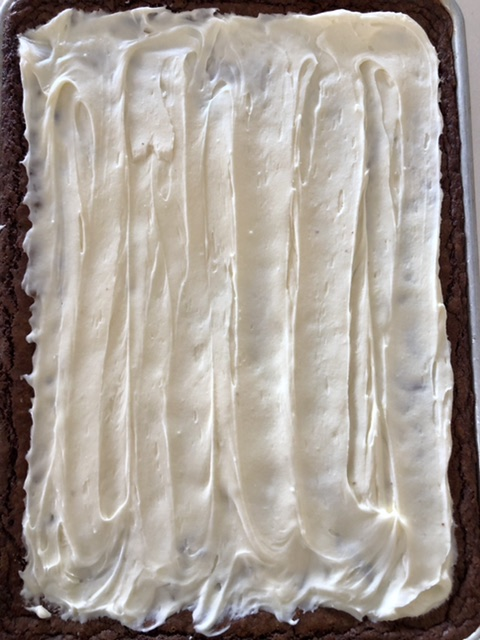 half sheet pan of cream cheese frosted brownies