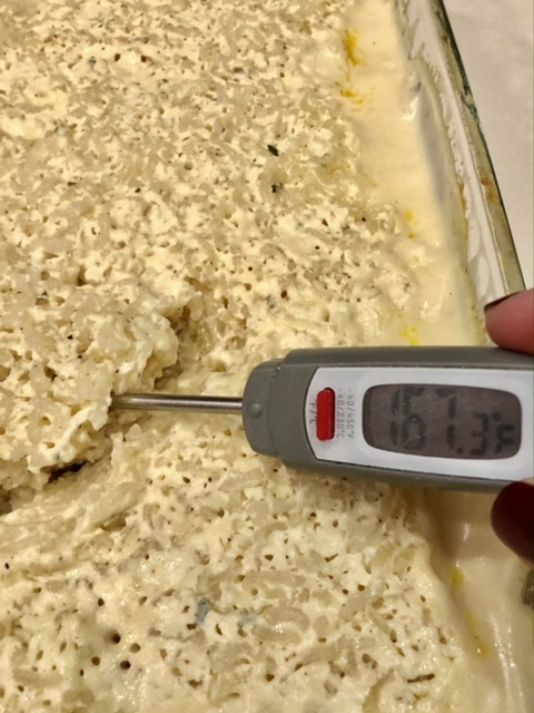 chicken and rice in a 9x13 pan cooked and the chicken being checked with a digital meat thermometer to make sure it has reached 165 degrees internal temperature
