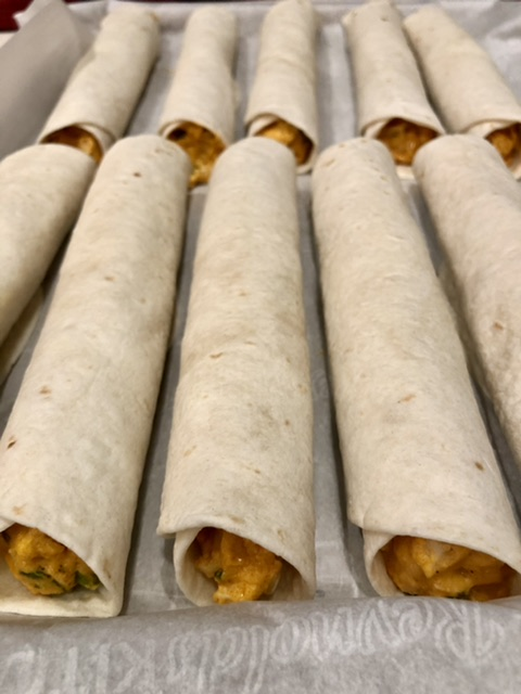 buffalo chicken taquitos rolled up lined up on a parchment paper lined baking sheet