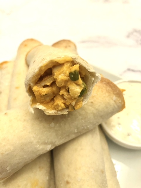 stack of buffalo chicken ranch taquitos with one cut open showing the filling