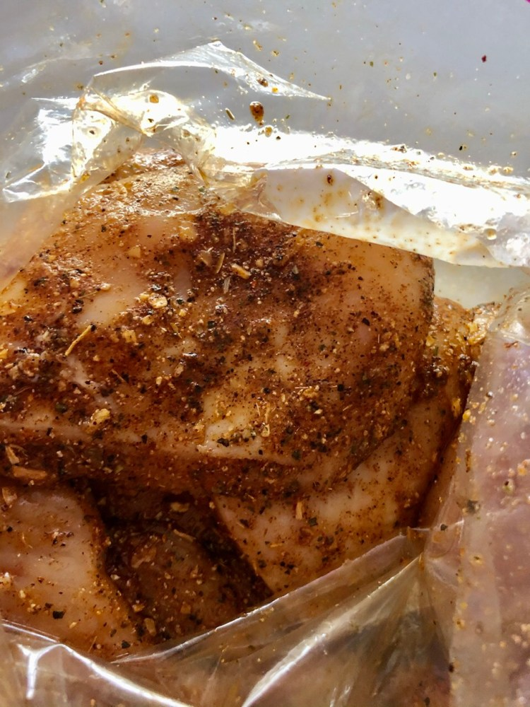 chicken in a zip top bag covered with taco seasoning