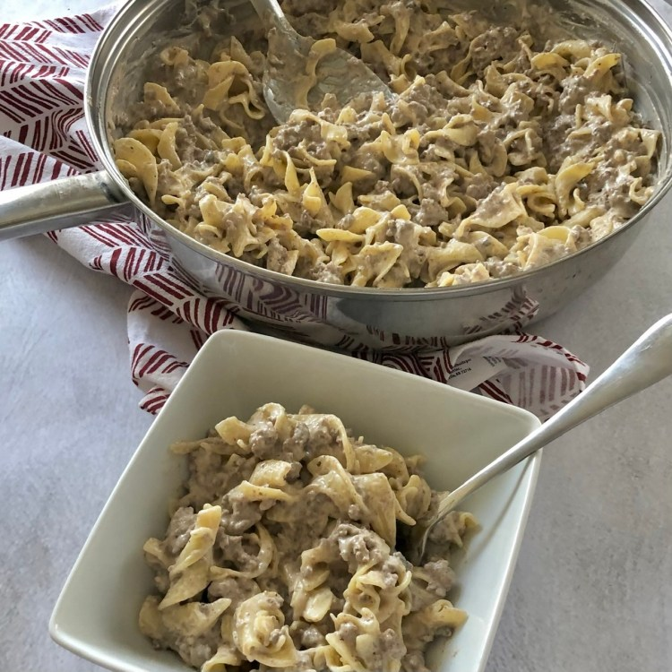 up close shot of ground beef stroganoff in the skillet and in a dish