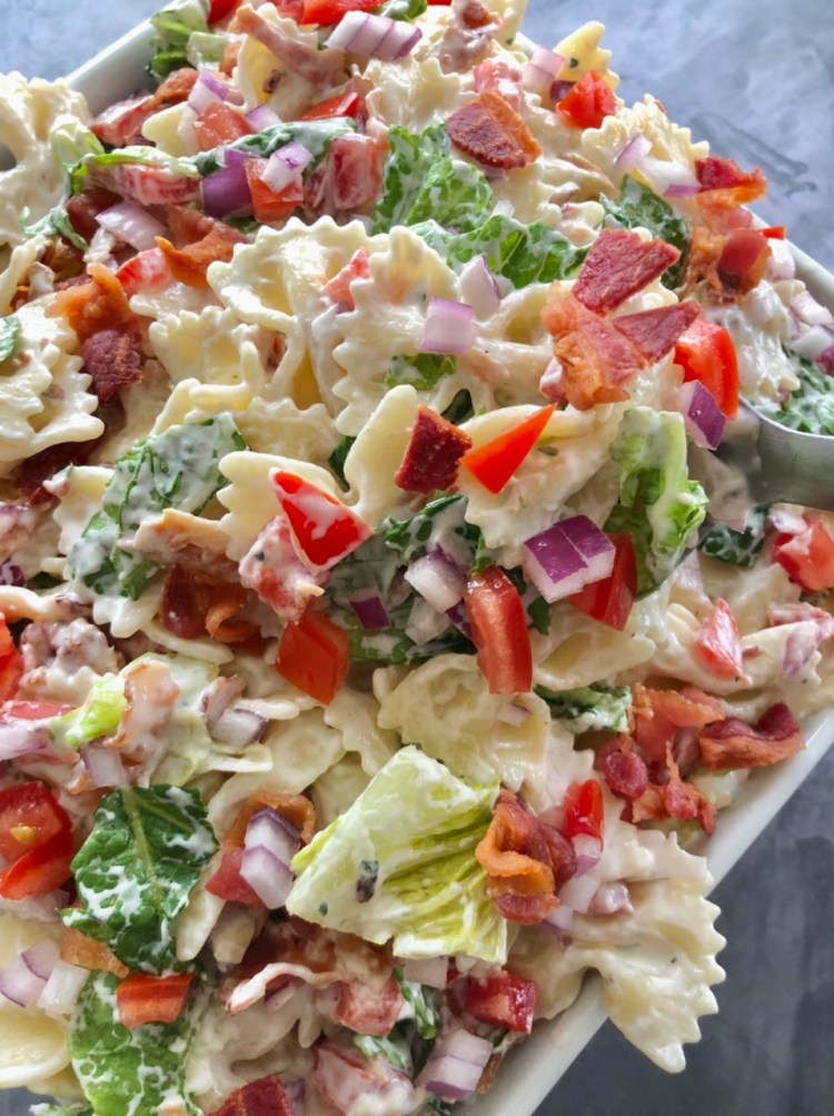 Close up shot of a bowl of BLT Ranch pasta salad with lettuce, bacon, tomatoes, red onions, bow tie pasta in a ranch dressing