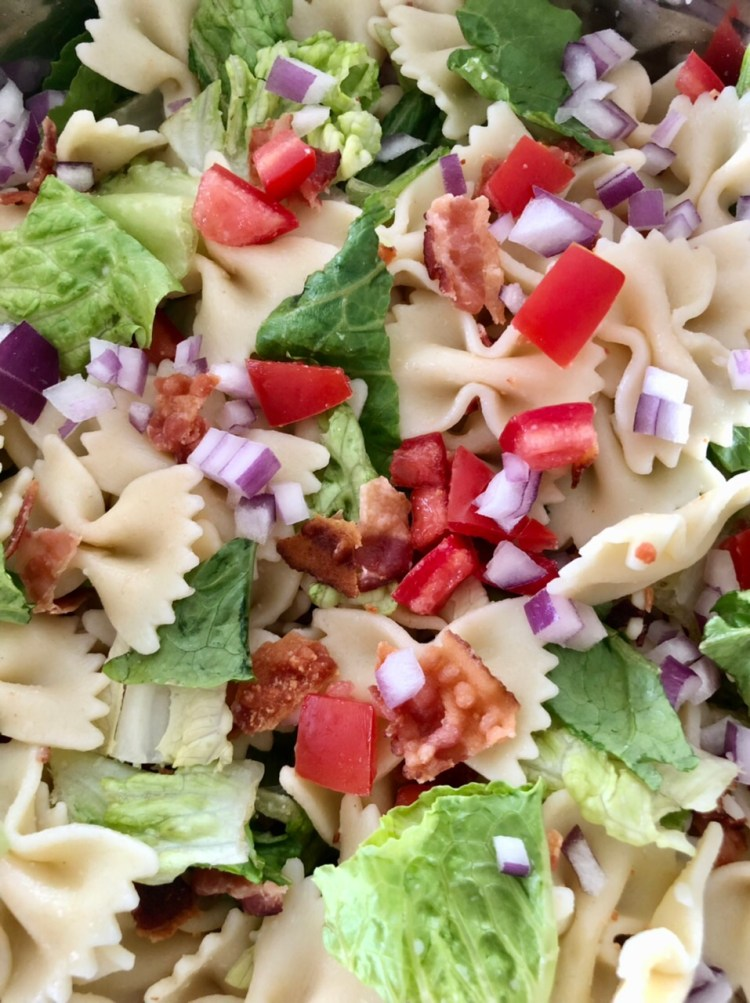 bacon, lettuce, tomatoes, onion and pasta all mixed up ready to add ranch dressing to the salad