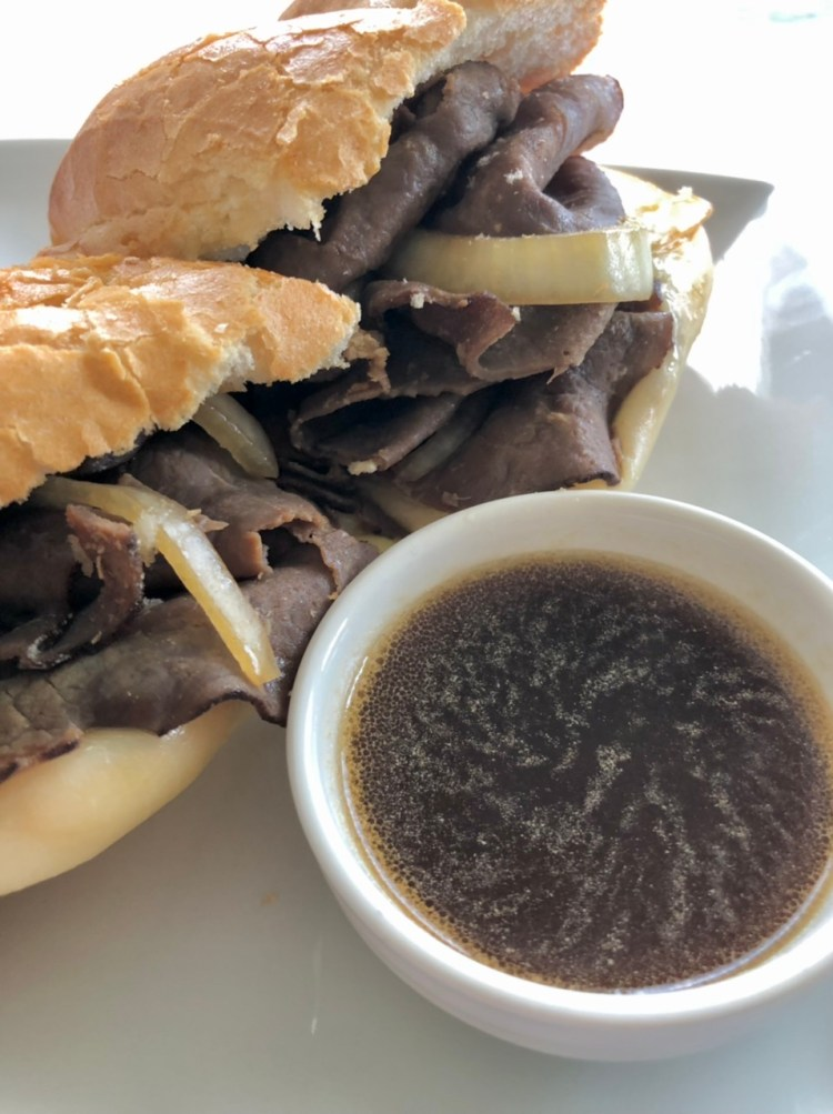 French Dip sandwich with onions sitting next to a dish of au jus sauce for dipping