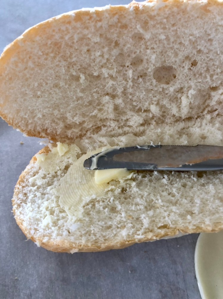 sliced hoagie bun with butter being spread on it