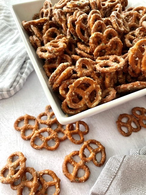 above shot of butter ranch pretzels in white bowl with some pretzels out of the bowl beside it
