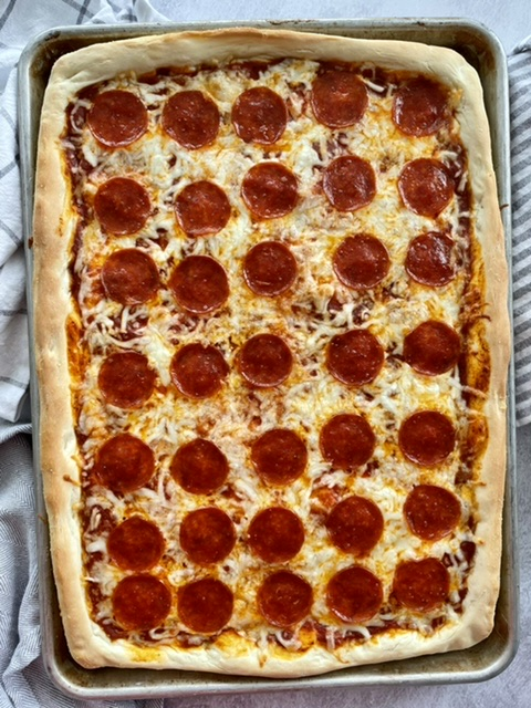 baked sheet pan pizza with pepperoni on it