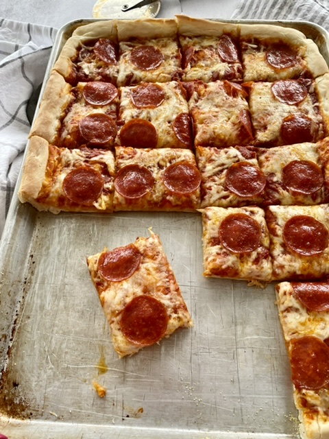 sheet pan pizza with sliced taken out of the pan