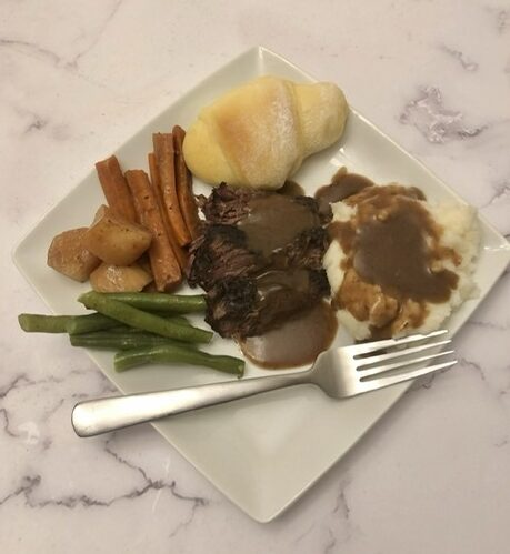 plate of pot roast with gravy, a roll, green beans, carrots and potatoes