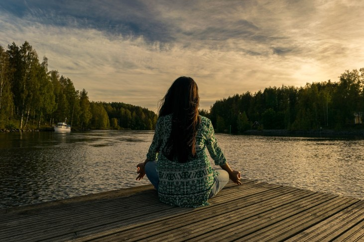 Woman practicing meditation & mindfulness in front of a lake