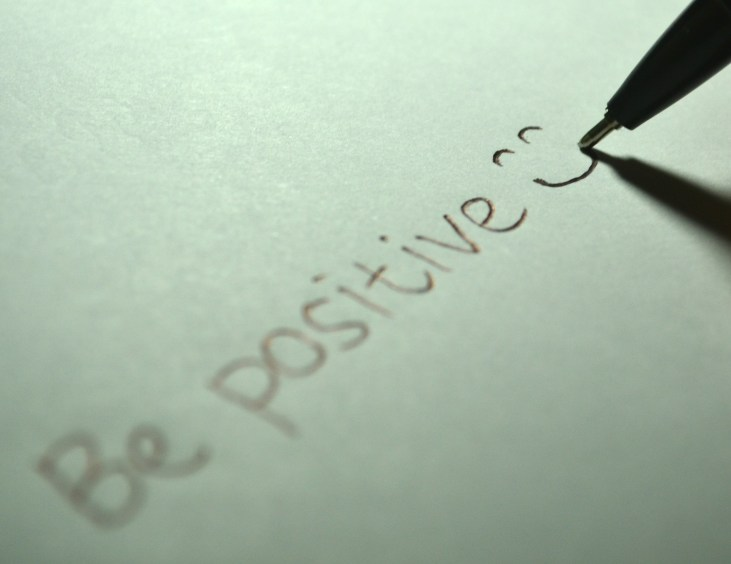 "Positivity, mental health. The words ""be positive"" written on a page with a smiley face"