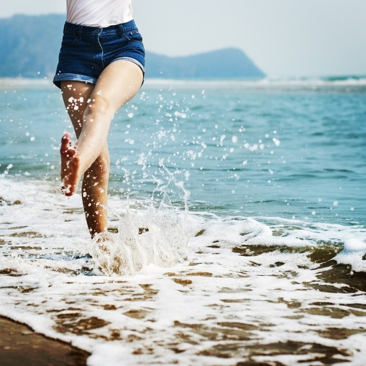 Woman splashing barefoot in the ocean. Self-care for summer