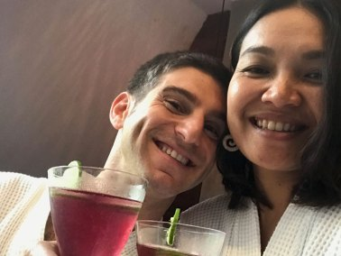 honeymoon couple travelers wearing white bathrobes with purple butterfly pea cocktails in their hotel room