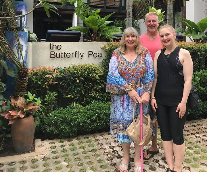 happy guests standing in front of the butterfly pea boutique hotel
