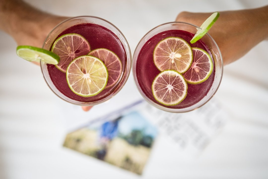 two people cheering with their two butterfly pea cocktails