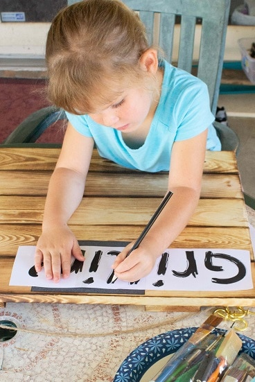 little girl tracing letters onto a wooden board