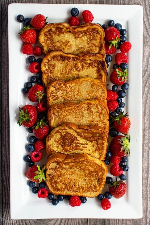 6 slices of french toast arranged in a line surrounded by strawberries, blueberries and raspberries.