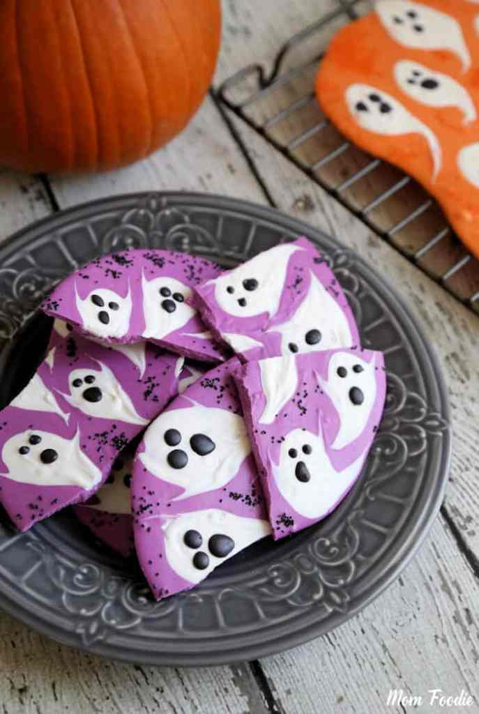 purple chocolate bark broken into pieces with white ghosts painted on there.  Piled on a grey serving dish - pumpkin in the background.