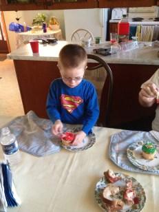 Aiden unwrapping cupcake at Mama & Papa's