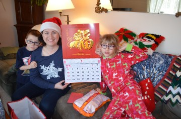 Melissa, Abby and Aiden holding a calendar from Sandra celebrating the Year of the Monkey, which is the year that Melissa and I were born in.