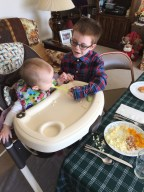 Aiden helping to feed Eva at Easter dinner
