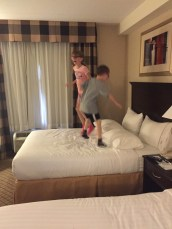 Abby & Aiden jumping on bed in hotel room