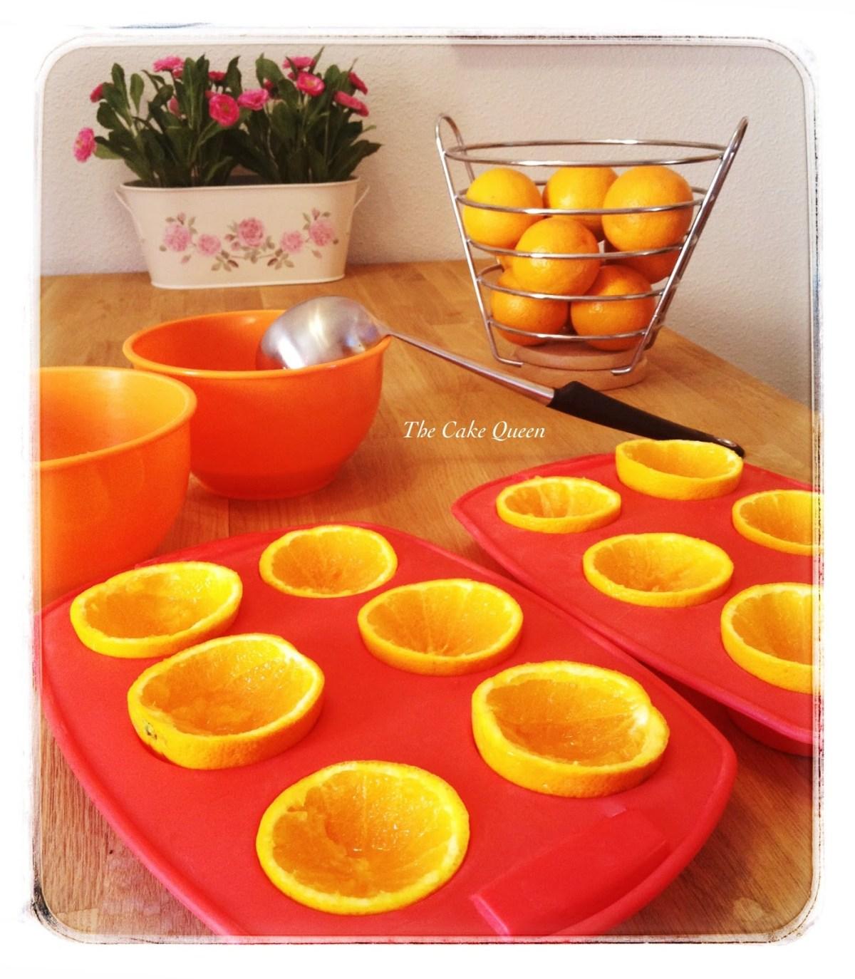 Coloca tus naranjas partidas por la mitad en bandejas para cupcakes