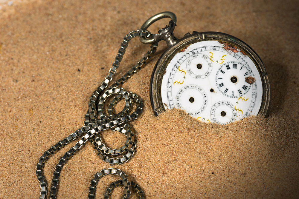 broken pocket watch in the sands of time