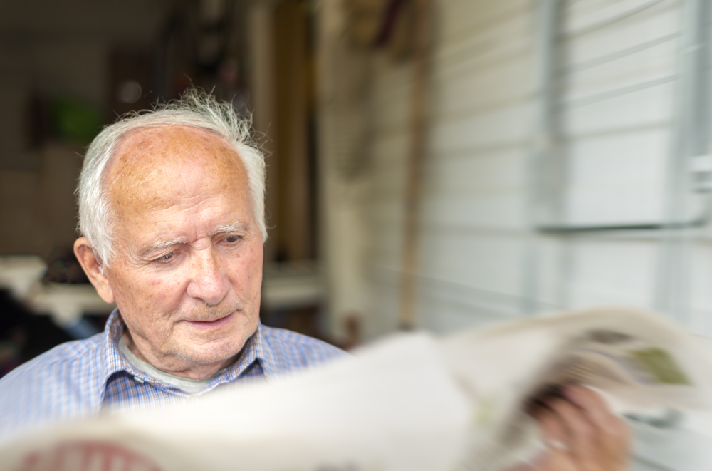 Elderly man reading newspaper, front view.
