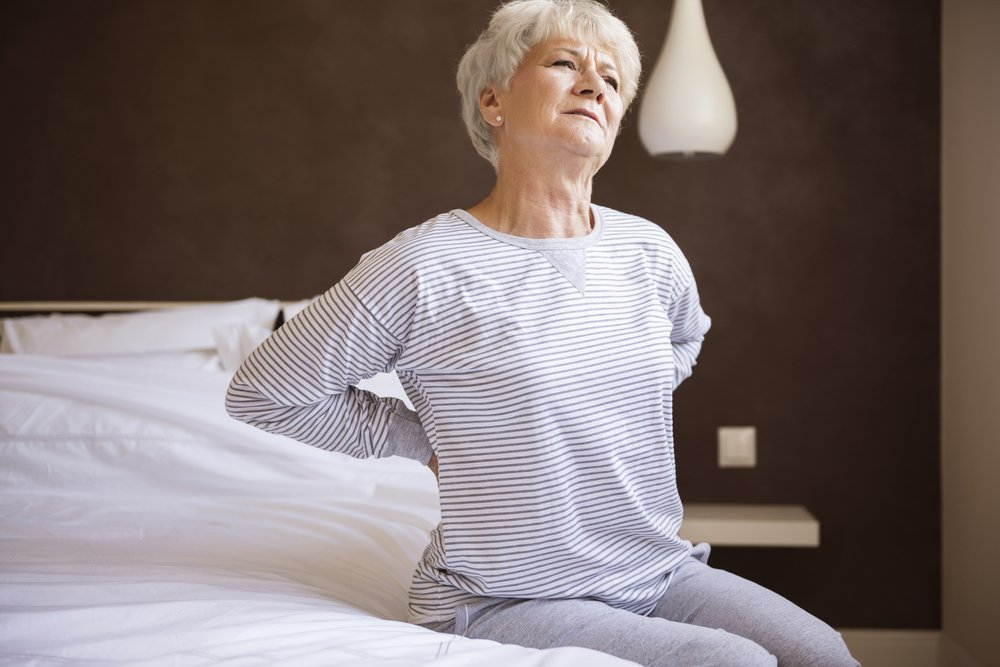 exhausted long-term caregiver suffering from back pain