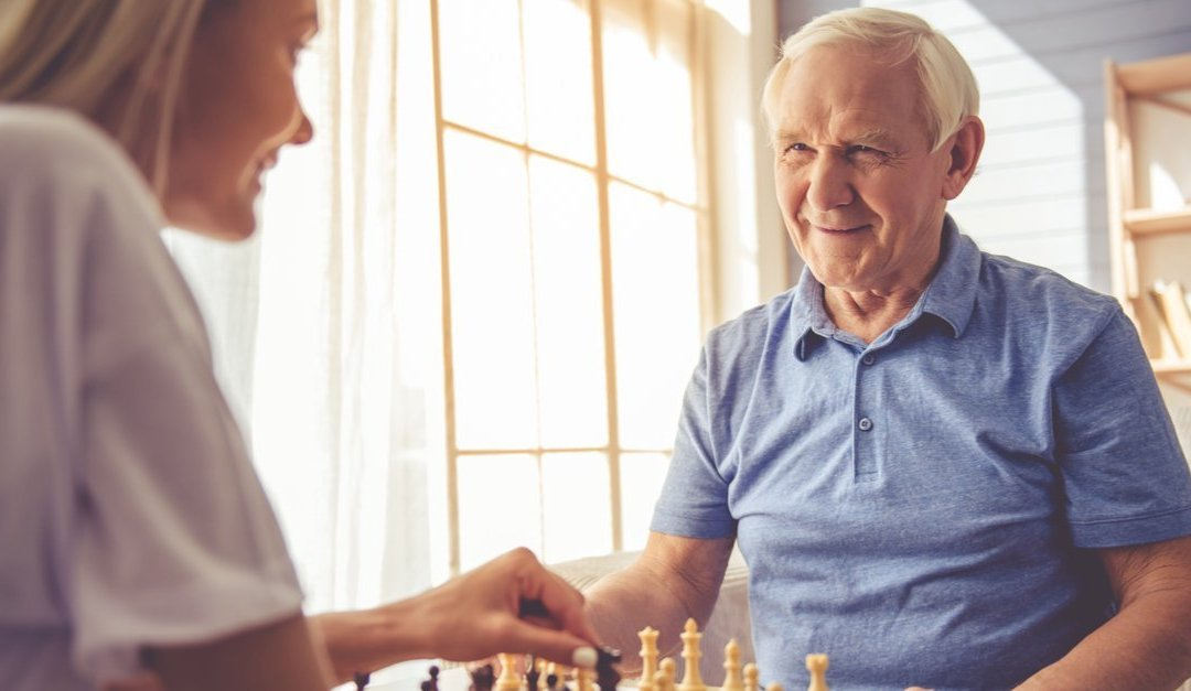 young hospice worker and elderly hospice patient play chess