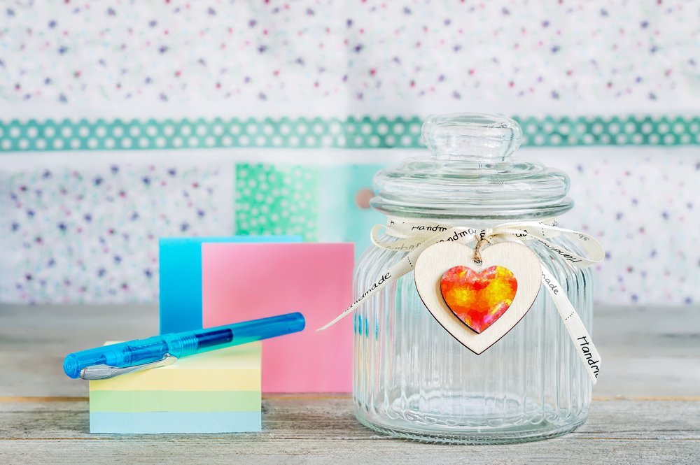 jar decorated with a heart next to a stack of note paper and a pen