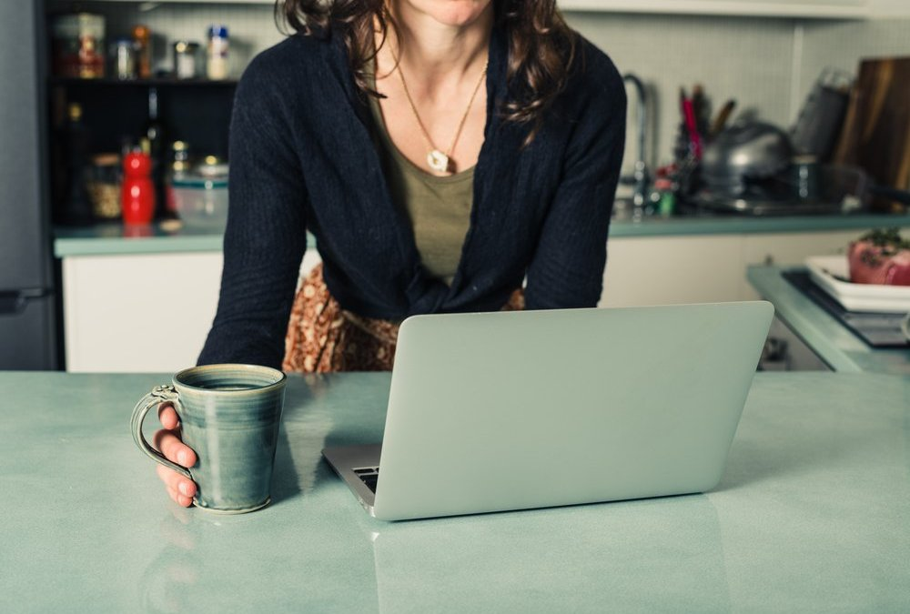 A young woman is using her laptop in a kitchen and is having a cup of coffee