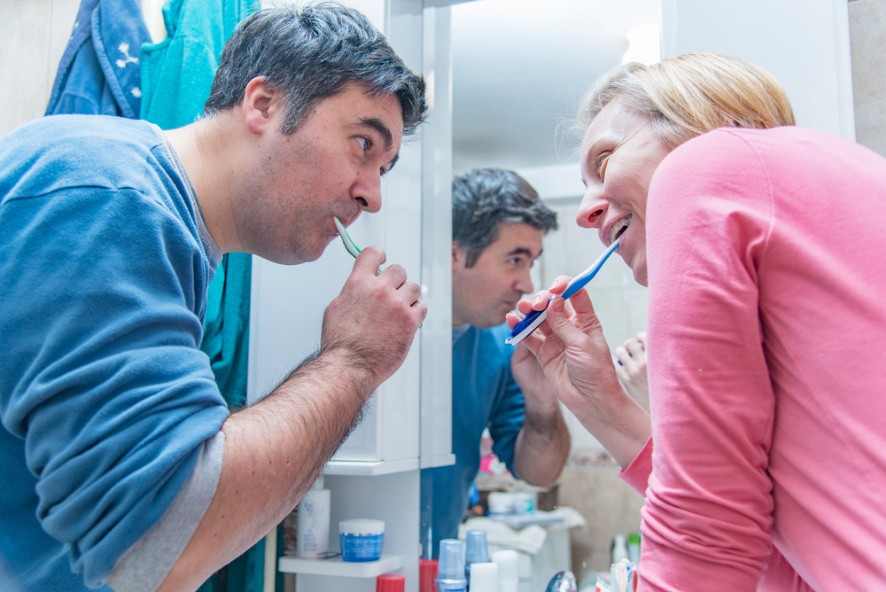 husband and wife in the bathroom laughing at each other while brushing their teeth