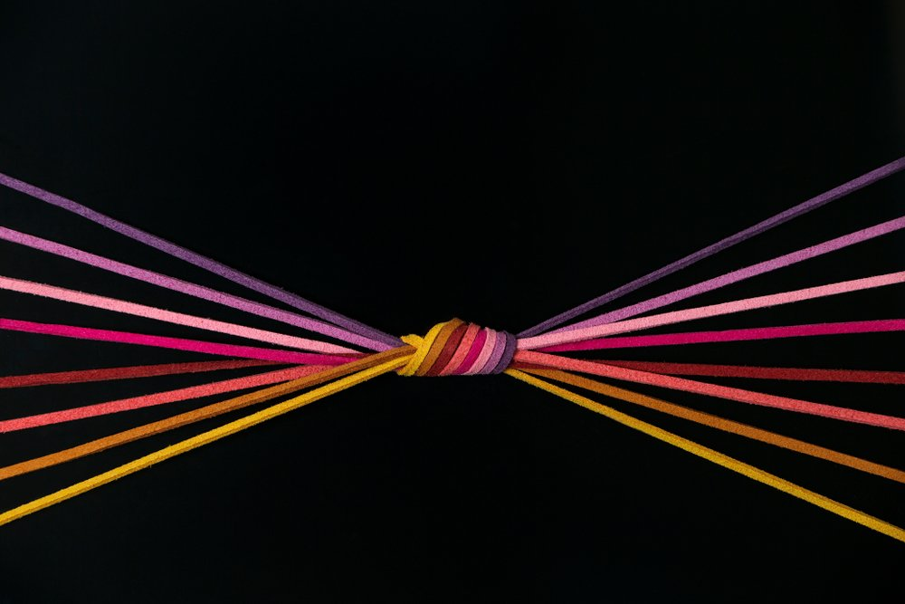 a bunch of string knotted on a black background. 8 eight color Thread String in a radial forms