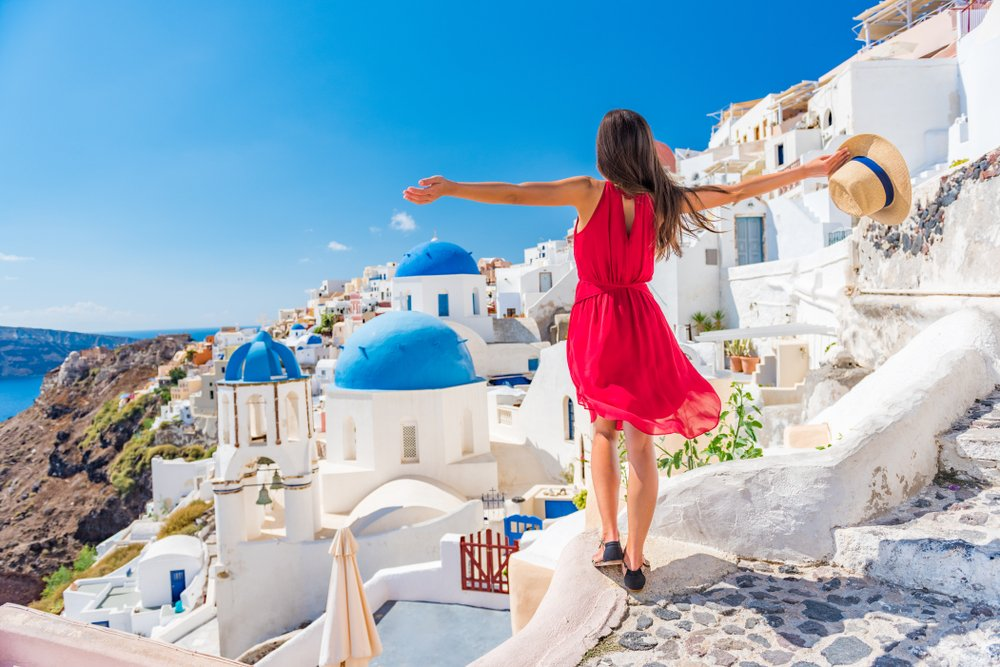 Europe travel vacation fun summer woman dancing in freedom with arms up happy in Oia, Santorini, Greece island. Carefree girl tourist in European destination wearing red fashion dress
