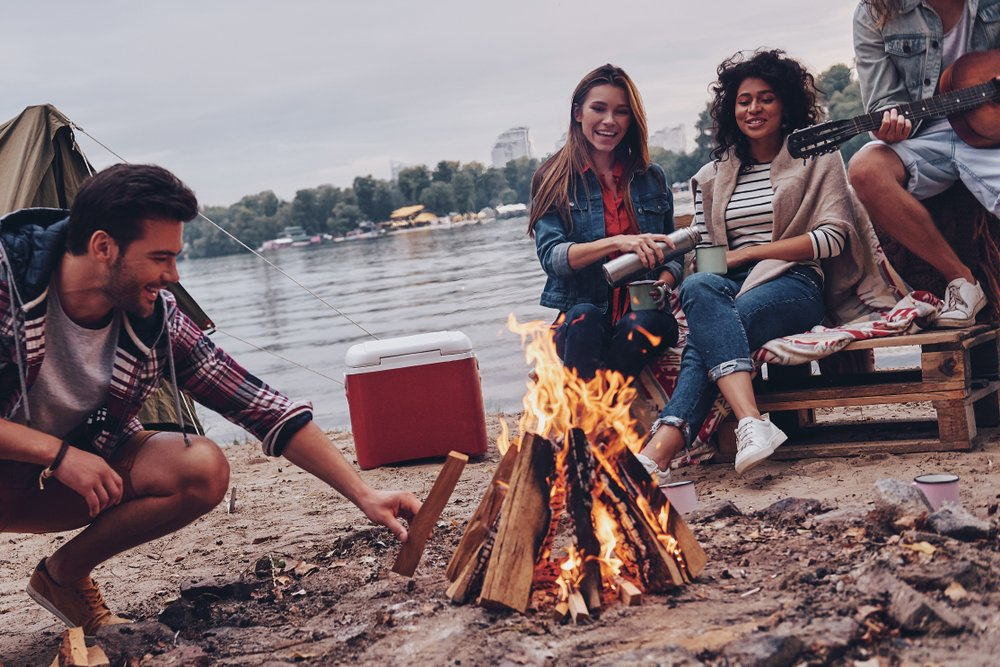 group of millennials having a bonfire on the beach and talking