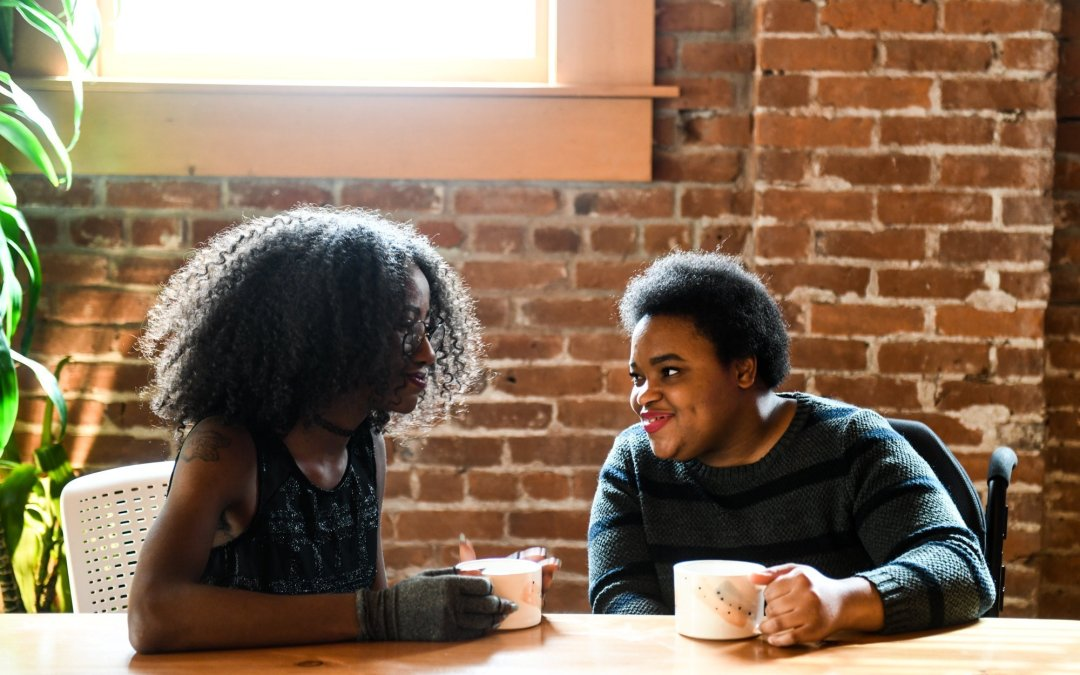 Two disabled Black women (one wearing compression gloves, and the other in a power wheelchair) on a date. Both are illuminated by natural light coming through a window while they hold coffee mugs, sit, and chat.