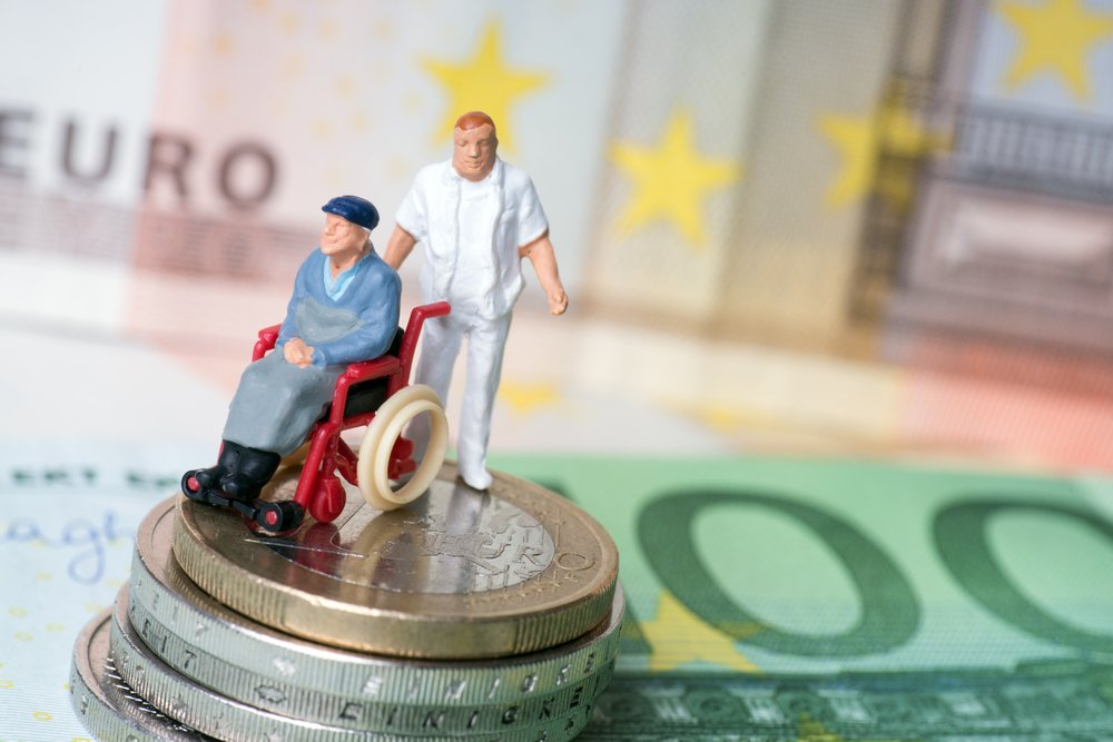 figurine of a wheelchair user and personal care attendant on a stack of euro coins with paper euros in the background, illustrating public long term scare insurance in europe