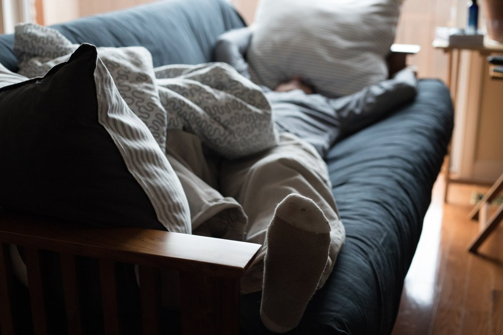 person laying exhausted on a futon. their face is obscured by a pillow
