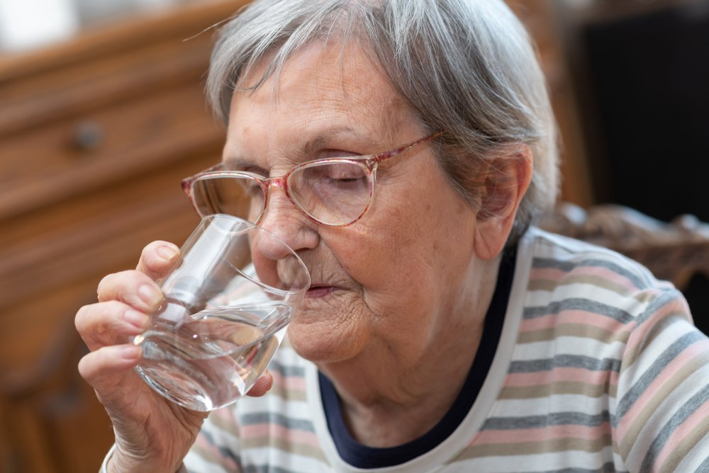 Elderly woman drinking water at home