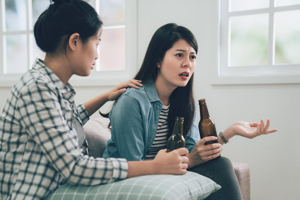 asian woman complaining telling to friend about her problems sitting on couch sofa at home. two girls holding bottle of beers drinking. roommate concentrated listening to lady and comforting her.