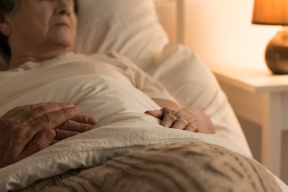 Close-up of a person supporting a sick, bedridden family member at home